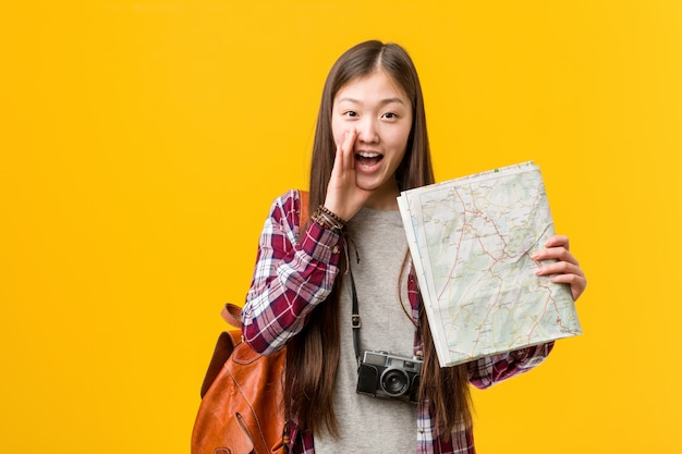 Young asian woman holding a map shouting excited to front
