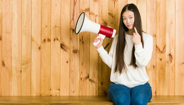 Young asian woman holding a megaphone pointing with finger at you as if inviting come closer.