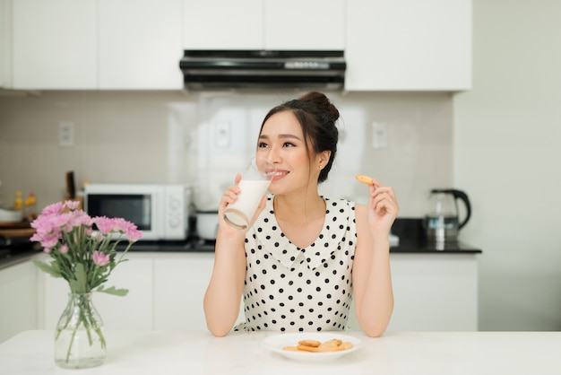 彼女の台所で乳白ガラスバイトクッキーを保持している若いアジアの女性