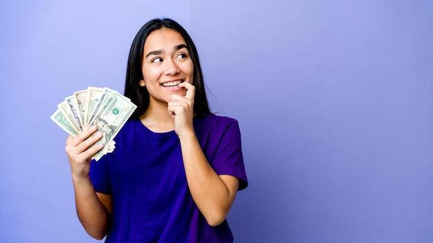紫色で隔離されたお金を保持している若いアジアの女性は、コピースペースを見ている何かについて考えてリラックスしました。
