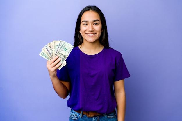 Молодая азиатская женщина, держащая деньги изолирована на фиолетовой стене, счастливая, улыбающаяся и веселая