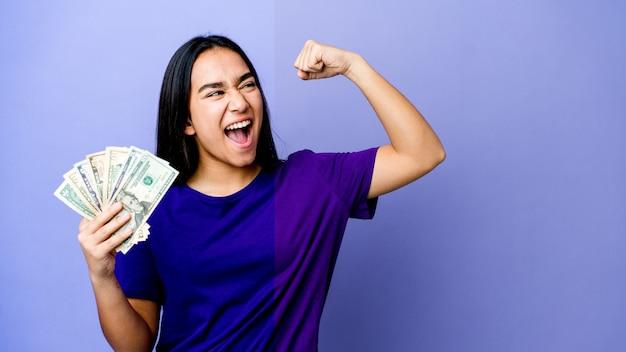 勝利、勝者の概念の後に拳を上げる紫色の壁に分離されたお金を保持している若いアジアの女性。