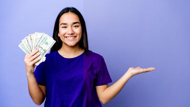 Молодая азиатская женщина держит деньги изолированными на фиолетовой стене, показывая место для копии на ладони и держа другую руку на талии