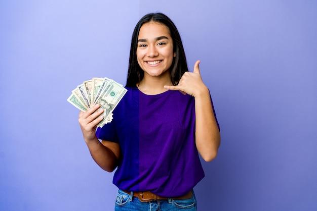 손가락으로 휴대 전화 제스처를 보여주는 보라색 벽에 고립 된 돈을 들고 젊은 아시아 여자.