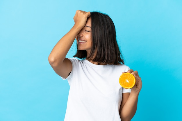 Young asian woman holding an orange isolated on blue has realized something and intending the solution