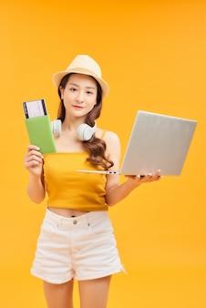 Молодая азиатская женщина, держащая паспорт и ноутбук