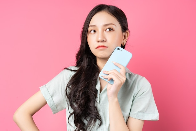 Young asian woman holding phone in her hand with pensive look on pink