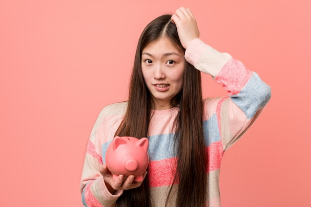 Young asian woman holding a piggy bank being shocked, she has remembered important meeting.