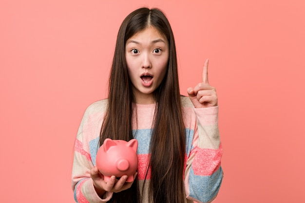 Young asian woman holding a piggy bank having some great idea