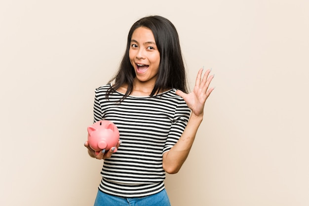 Young asian woman holding a piggy bank receiving a pleasant surprise, excited and raising hands.