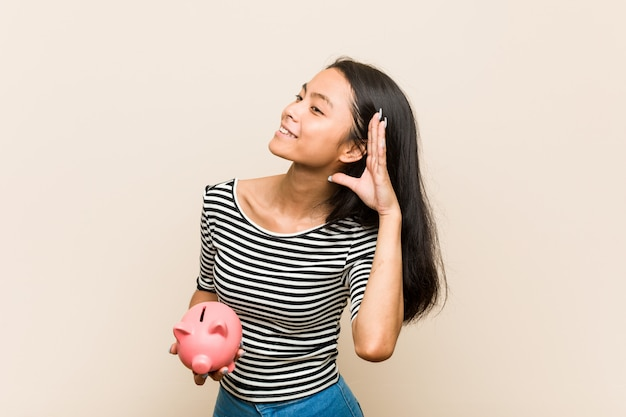Young asian woman holding a piggy bank trying to listening a gossip.