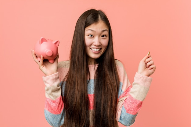 Young asian woman holding a piggy bank