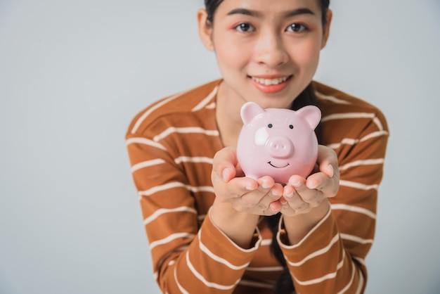 Young asian woman holding piggy bank