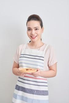 自家製チョコレート クッキーとプレートを保持している若いアジアの女性