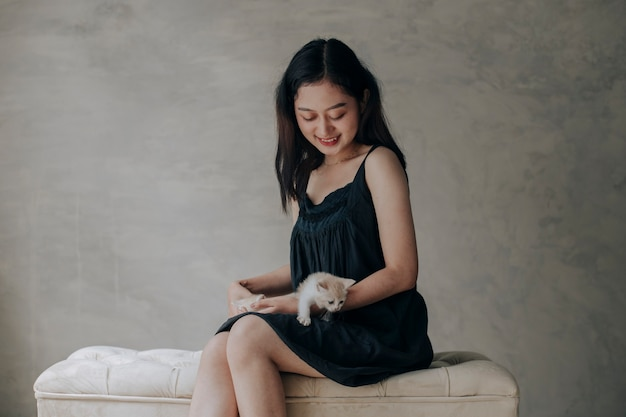 Young asian woman holding and playing with her cute kitten cat with lovely moment
