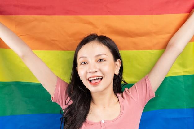 파란색에 lgbtq + 커뮤니티를 지원하기 위해 무지개 깃발을 들고 젊은 아시아 여성