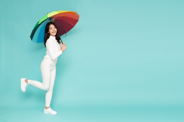Young asian woman holding rainbow umbella standing isolated on green background, full body