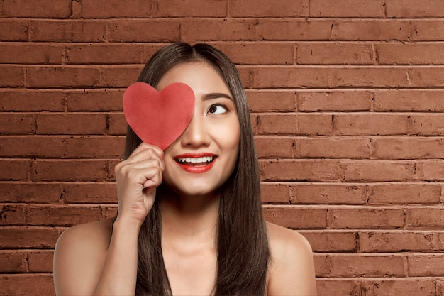 Young asian woman holding red heart