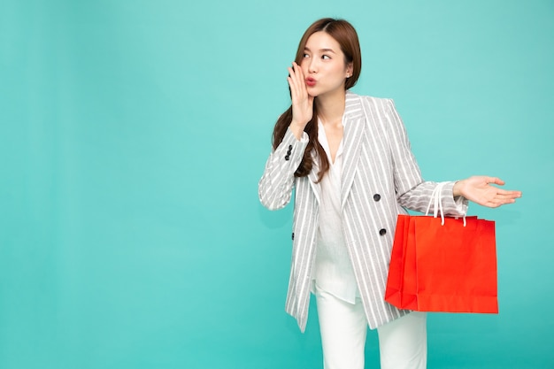 Young asian woman holding red shopping bags isolated on green background