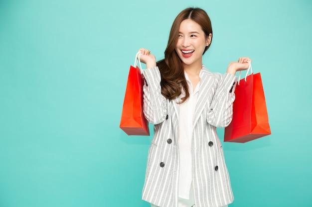 Молодая азиатская женщина, держащая красные хозяйственные сумки, изолированные на зеленом фоне