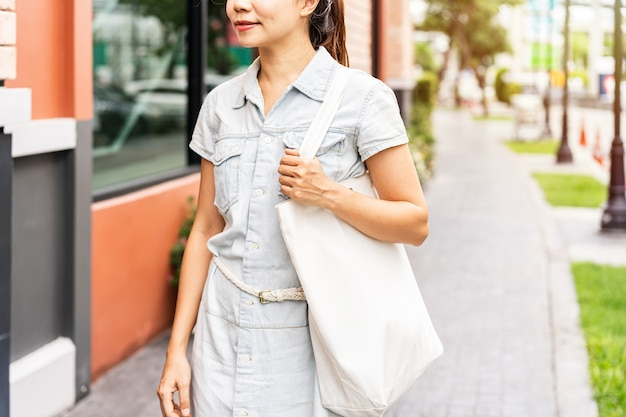 Young asian woman holding a reusable bag and walking in the city, zero waste concept