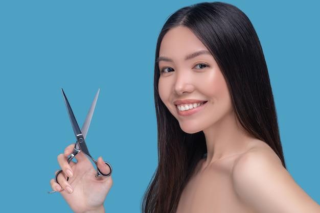 はさみを持って笑っている若いアジアの女性