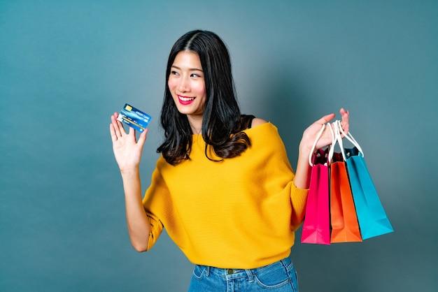 노란색 셔츠에 쇼핑백과 신용 카드를 들고 젊은 아시아 여자