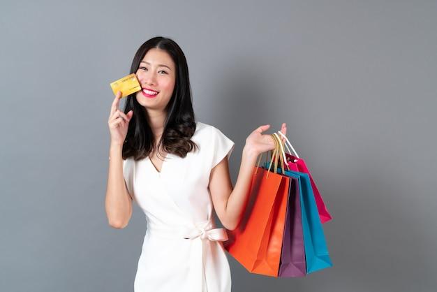 Молодая азиатская женщина, держащая хозяйственные сумки и кредитную карту