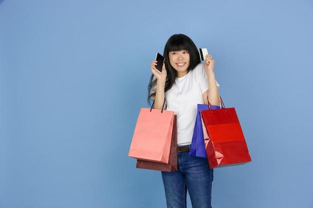 Giovane donna asiatica che tiene le borse della spesa su blue
