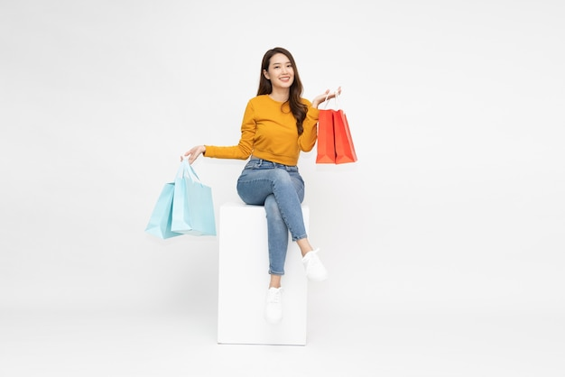 Young asian woman holding shopping bags and sitting on white box isolated on white background