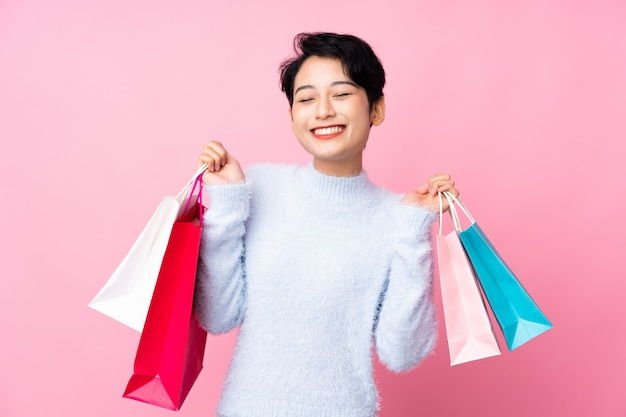 Young asian woman holding shopping bags and smiling