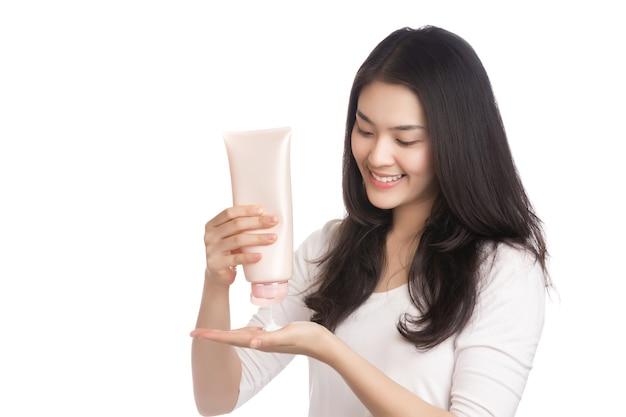白で隔離のスマイリーフェイスとスキンケアクリームを保持している若いアジアの女性。