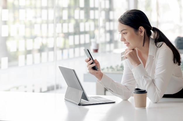 Молодая азиатская женщина держа смартфон и кредитную карту, сидя за офисным столом.