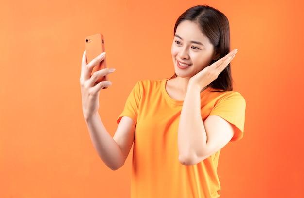 オレンジ色のスマートフォンを保持している若いアジアの女性