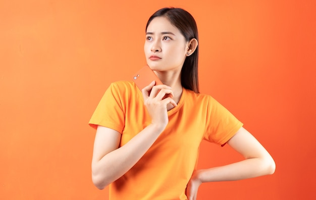 Young asian woman holding smartphone on orange
