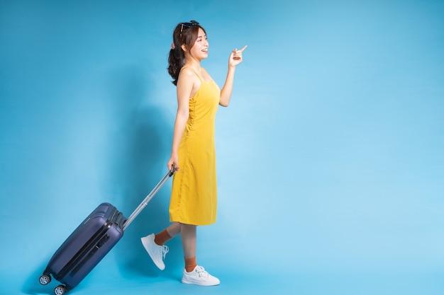 Молодая азиатская женщина, держащая чемодан на синем, летнем концепте
