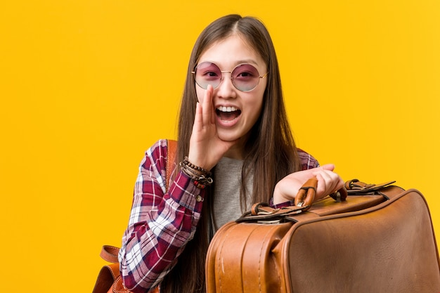 Young asian woman holding a suitcase shouting excited to front.