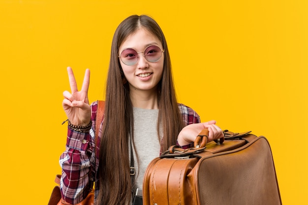 Young asian woman holding a suitcase showing number two with fingers.