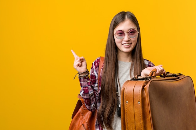 Young asian woman holding a suitcase smiling cheerfully pointing with forefinger away.