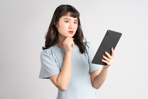 Young asian woman holding tablet on white
