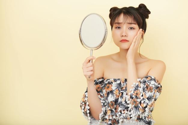 젊은 아시아 여자 손 거울을 들고 불행한 얼굴로 카메라를 찾고