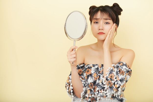 Young asian woman holding up hand mirror and looking at camera with unhappy face