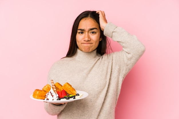 Young asian woman holding a waffle being shocked