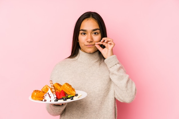 Young asian woman holding a waffle isolated with fingers on lips keeping a secret.