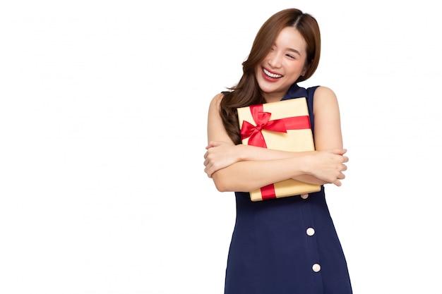 흰색 배경 위에 절연 골드 선물 상자를 포옹하는 젊은 아시아 여성