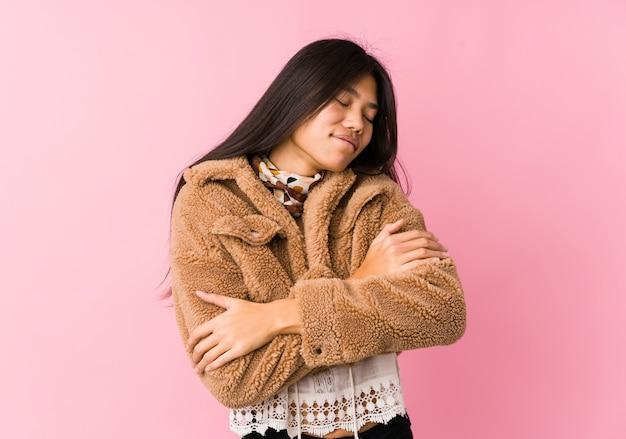 Молодая азиатская женщина обнимает, улыбается беззаботно и счастливо.