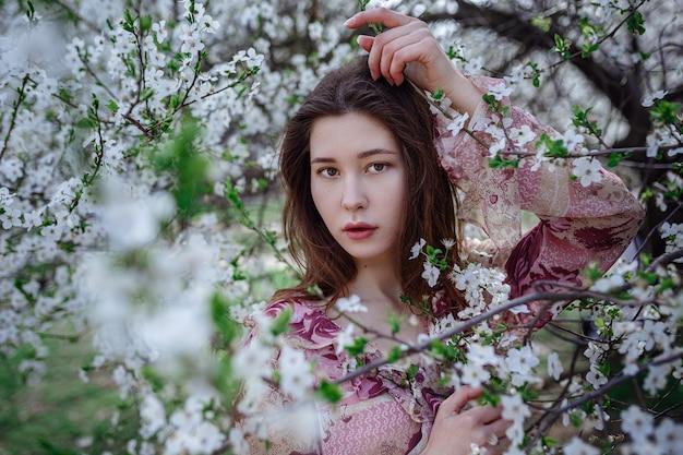 Молодая азиатская женщина в цветущем саду. романтичный образ стильной повседневной женщины, модной шелковой блузки. позитивный настрой. в японии цветут пышные цветы cheery blossom.