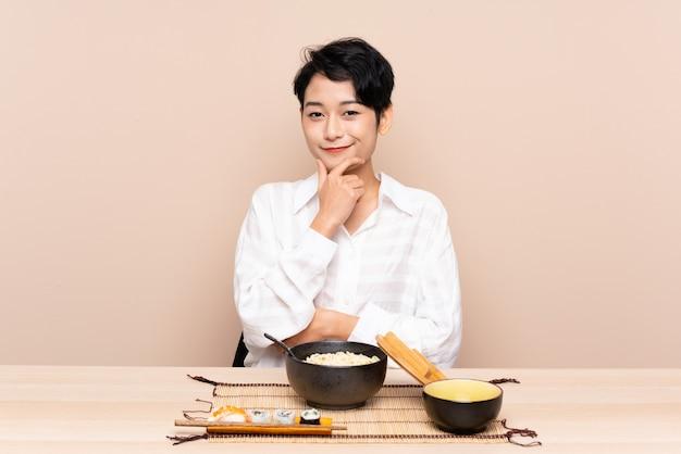 麺と笑い寿司のボウルを持つテーブルで若いアジア女性