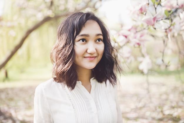 白いシャツの春の肖像画の若いアジアの女性