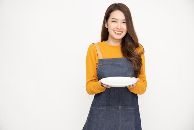 Молодая азиатская женщина в фартуке стоит и держит пустую белую тарелку, изолированную на белом фоне
